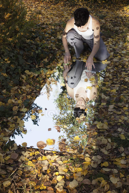 Woman sitting on ground and looking in mirror lying on foliage at park — Stock Photo