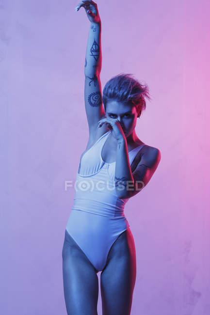 Portrait de jeune fille de la mode en maillot de bain une pièce posant avec le bras levé sur fond coloré — Photo de stock