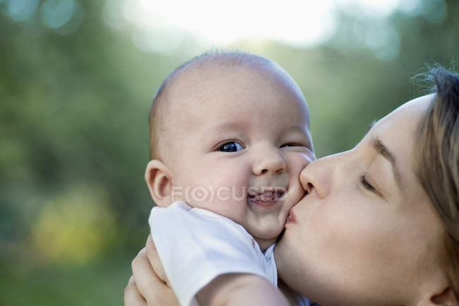 A mother kissing her baby boy — Stock Photo