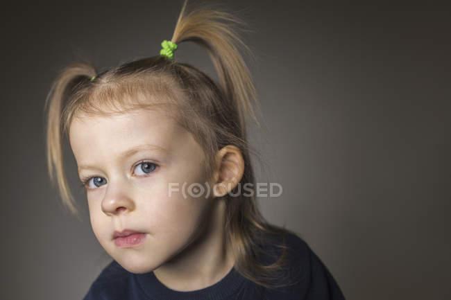 Portrait de gros plan de jolie fille avec des nattes sur fond gris — Photo de stock