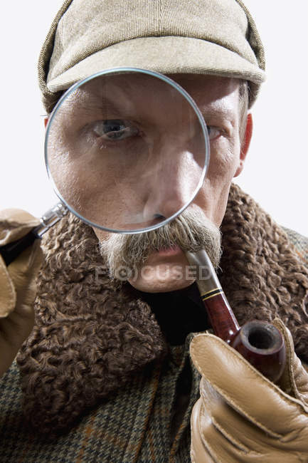 Close-up of man dressed up as Sherlock Holmes with magnifying glass distorting eye — Stock Photo