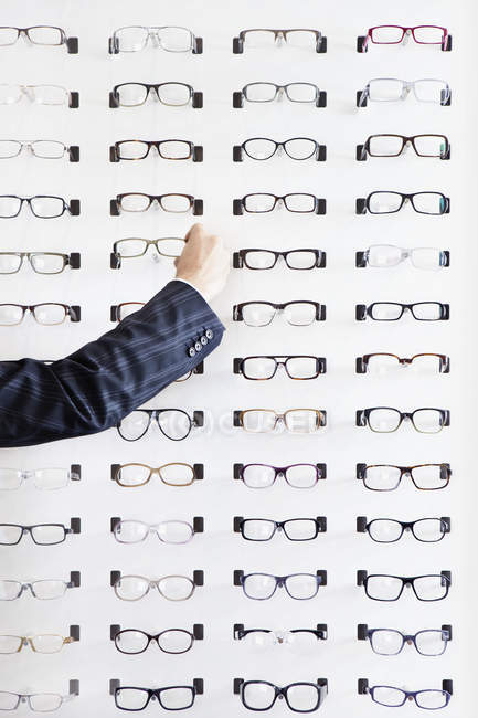 Crop human hand choosing pair of glasses in eyewear store — Stock Photo