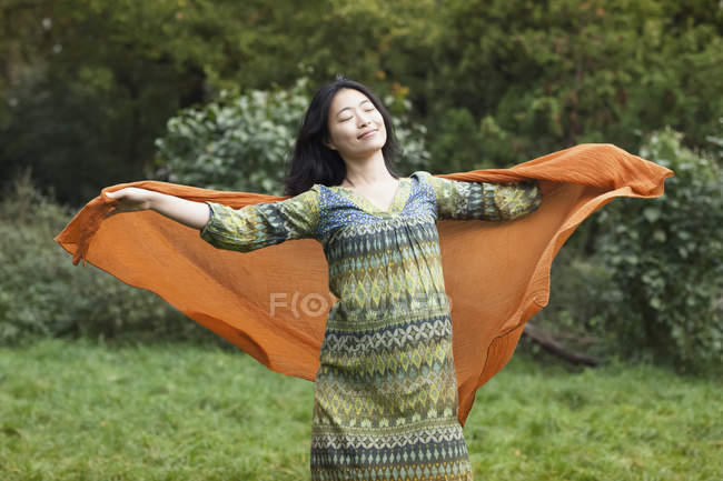 Three quarter length of woman posing with eyes closed and arms outstretched with orange scarf at park during autumn day — Stock Photo