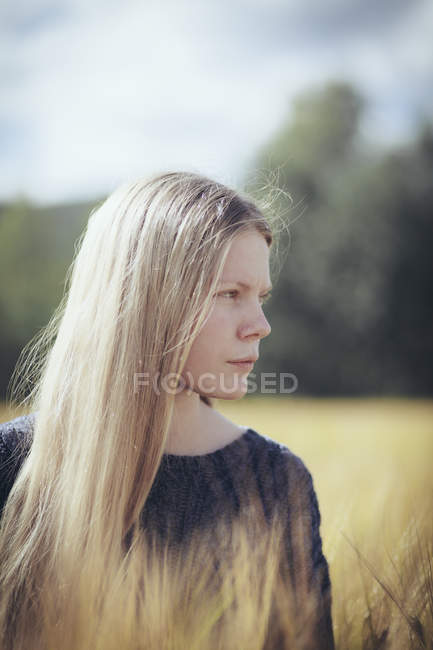 Portrait of thoughtful blonde woman with long hair posing at countryside field — Stock Photo