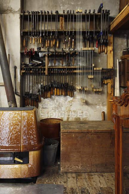 Varias herramientas colgadas en estantes en el taller de carpintería - foto de stock