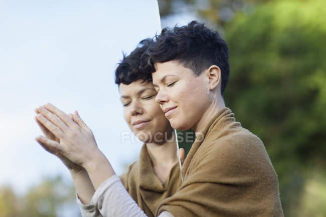 Ritratto di donna sorridente con gli occhi chiusi appoggiati sullo specchio al parco — Foto stock