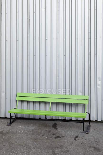 Зеленая скамейка перед стальным зданием — стоковое фото