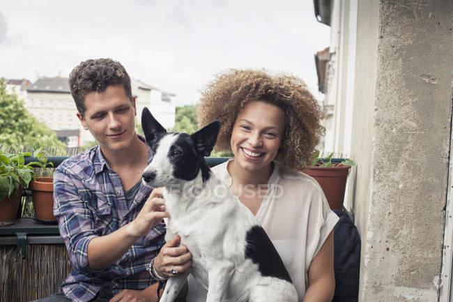 Retrato de mulher sorridente carregando cão sentado com amigo na varanda — Fotografia de Stock
