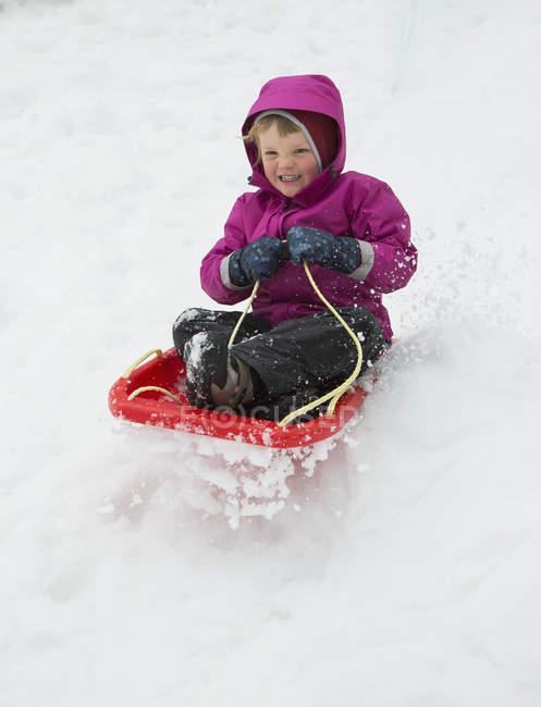 Portrait of boy tobogganing on snow field — Stock Photo