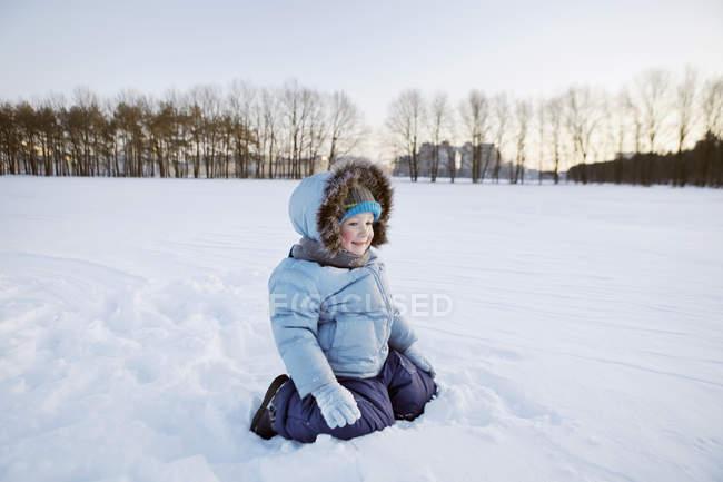 Un ragazzo che gioca nella neve durante il giorno — Foto stock