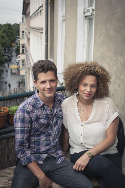 Портрет посміхаючись молода пара, сидячи на балконі — стокове фото