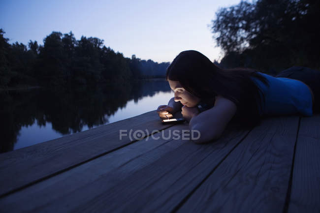A woman using an electronic organizer while lying on a jetty, dusk — Stock Photo