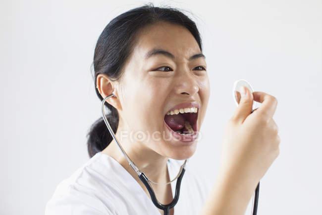 Разочарованный доктор кричать с открытым ртом в стетоскоп против белой стене — стоковое фото