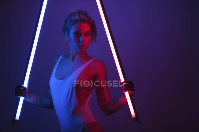 Portrait of young woman wearing swimsuit and posing with glowing lights tubes — Stock Photo