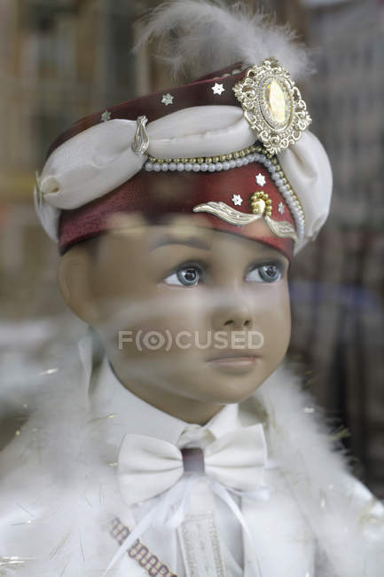 Boy mannequin wearing turban seen through glass — Stock Photo