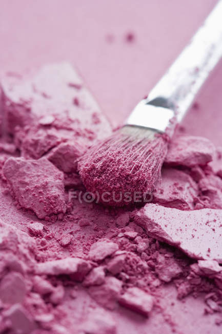 Crushed pink eye shadow and make-up brush — Stock Photo