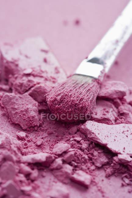 Crushed pink eye shadow and make-up brush — Stock Photo