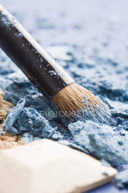 Crushed blue and beige eye shadow and make-up brush — Stock Photo