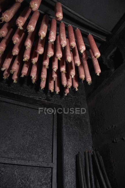 Visão de baixo ângulo de salame pendurado no fumeiro — Fotografia de Stock