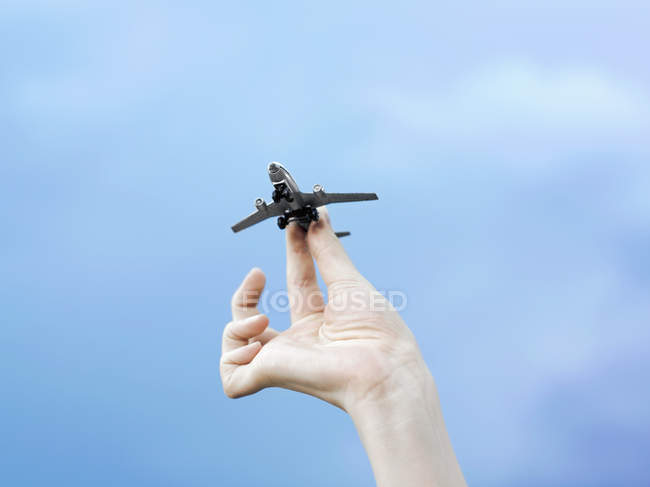 Crop female hand holding model airplane over sky — Stock Photo