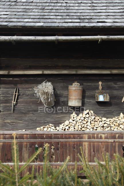 Facciata fienile con utensili appesi sopra tronchi accatastati — Foto stock