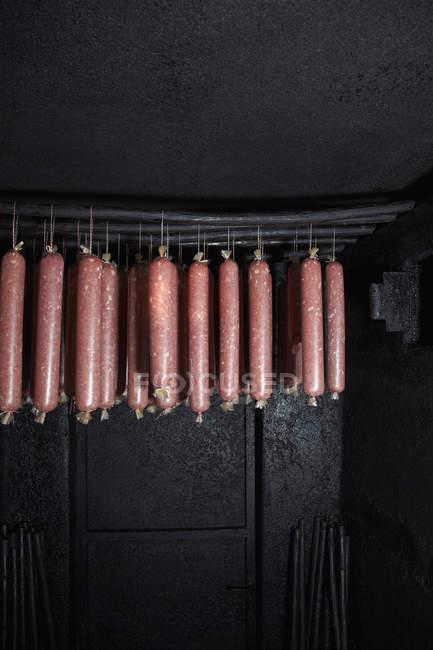 Linhas de salame penduradas em fumeiro — Fotografia de Stock