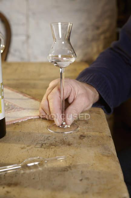 Main de mâle récolte avec verre de schnaps sur table — Photo de stock