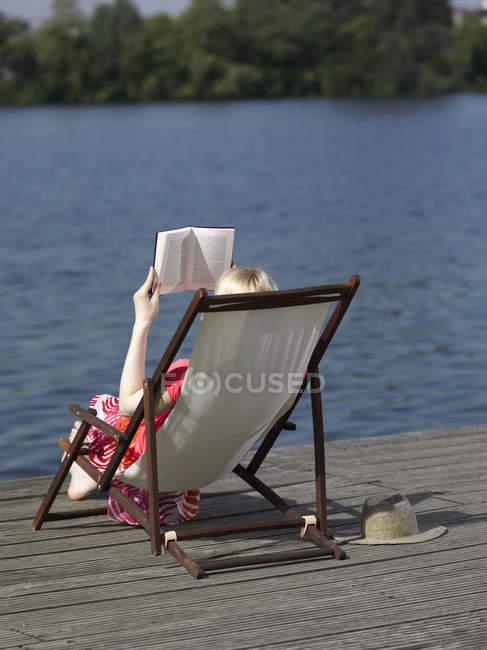Vista traseira da mulher lendo na cadeira de praia na doca — Fotografia de Stock