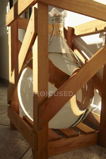 Grand verre bouteille de schnaps dans la Caisse — Photo de stock