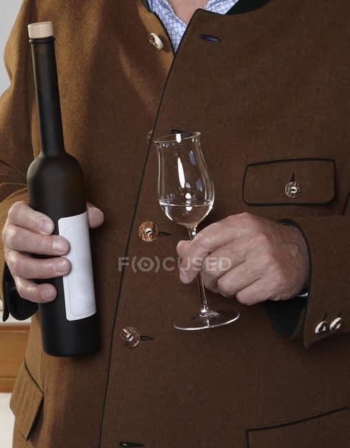Міделю чоловік тримає пляшку і скла шнапс — стокове фото