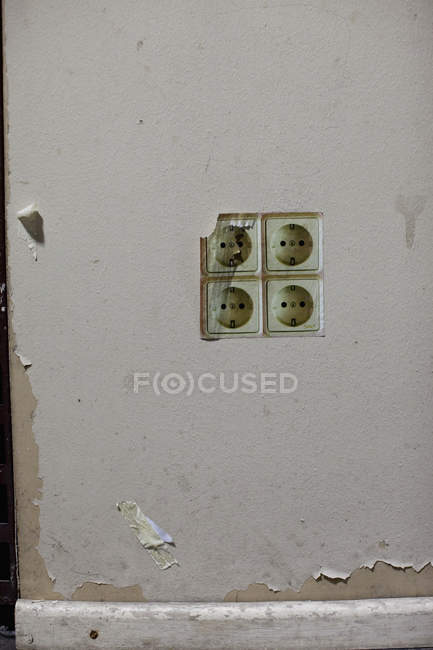 Vue de face des prises électriques sur le mur minable — Photo de stock