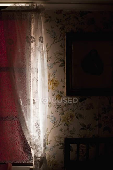 Detalhe do interior à moda antiga, com papéis de parede estampados florais e cortinas na janela — Fotografia de Stock