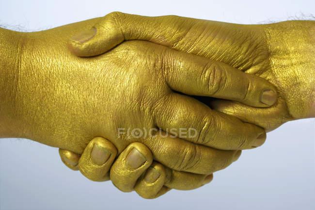 Ernte goldene Hand schüttelt über grauem Hintergrund — Stockfoto