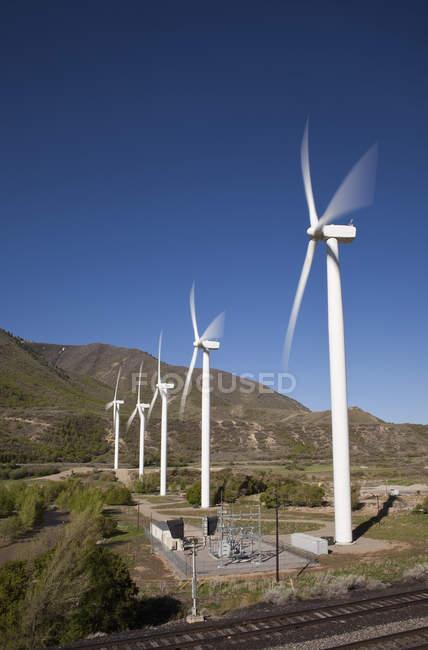 Строка ветровых турбин на горной долине — стоковое фото
