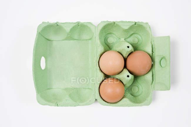 Diretamente acima vista de três ovos marrons com caixa de ovos — Fotografia de Stock