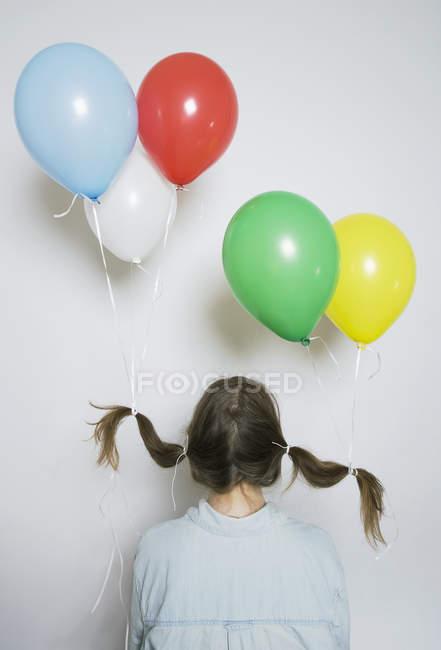 Вид сзади девочка с гелиевых шаров привязаны к косички — стоковое фото