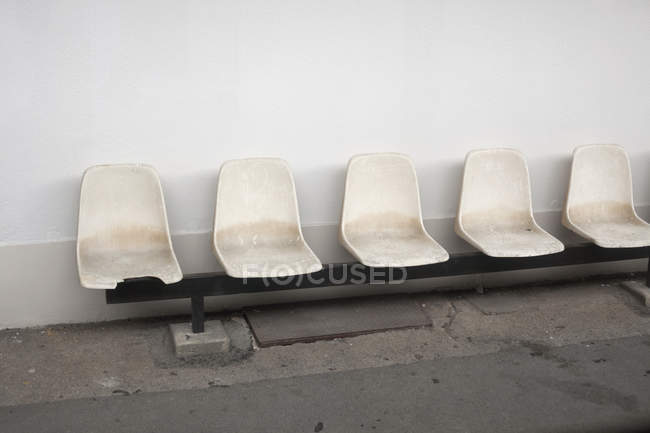 Row of empty plastic seats by wall — Stock Photo
