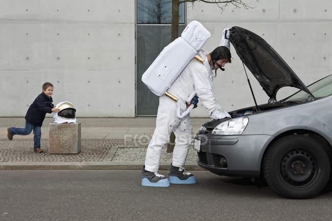 Un bambino che ruba un casco spaziale mentre un astronauta ripara la sua auto rotta — Foto stock