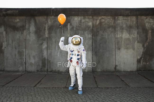 Astronaut on city sidewalk holding a balloon — Stock Photo