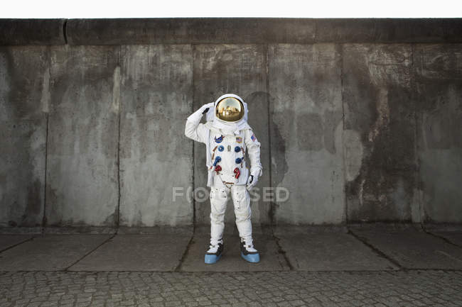 Saluting astronaut posing on sidewalk in city — Stock Photo