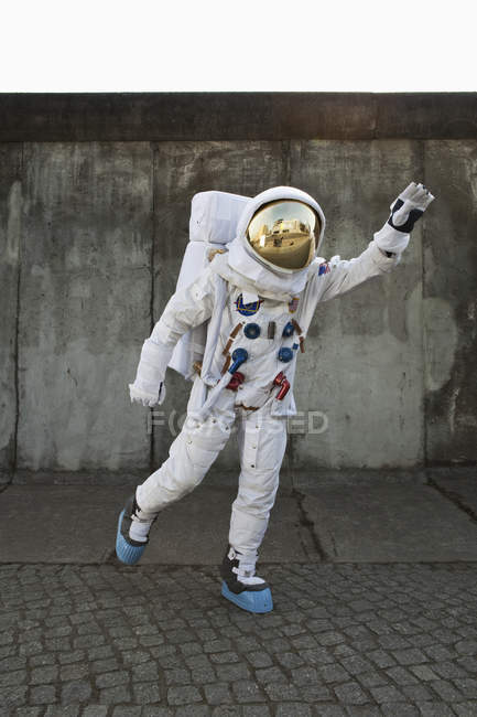 Astronaut on city sidewalk pretending to take off in flight — Stock Photo