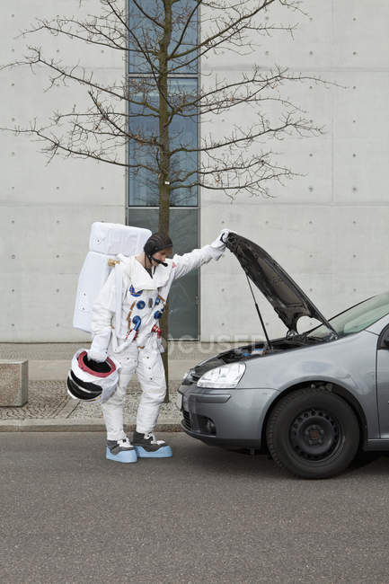 An astronaut with car troubles — Stock Photo