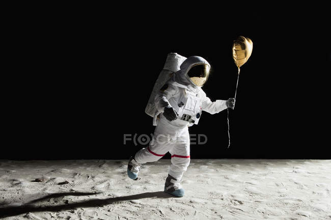 Astronaut walking with heart shaped helium balloon on moon — Stock Photo