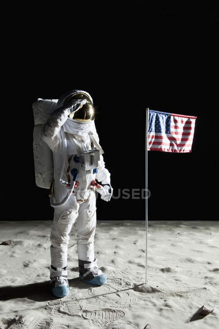 Astronaut on surface of moon saluting American flag — Stock Photo