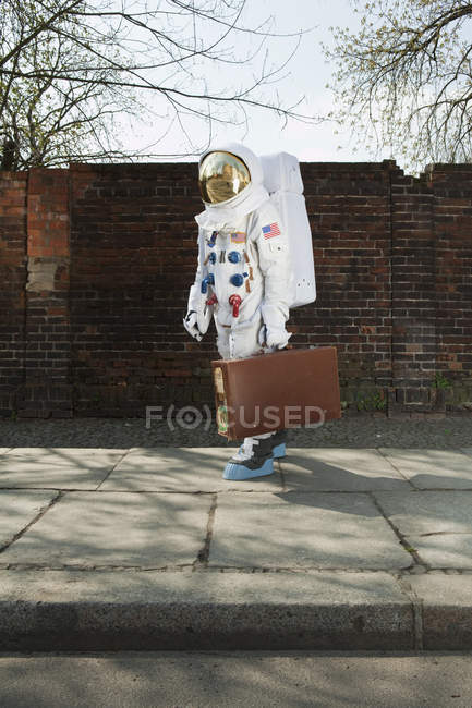 Astronaut walking on city sidewalk and carrying suitcase — Stock Photo