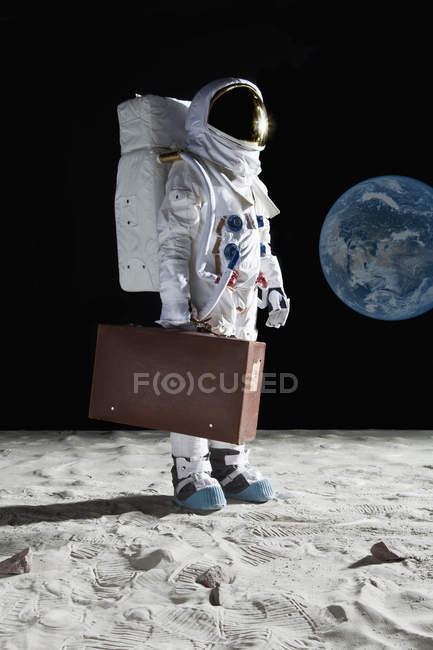 Astronaut carrying suitcase on moon — Stock Photo