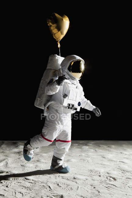 Astronaute marchant sur la lune et tenant un ballon d'hélium en forme de coeur — Photo de stock