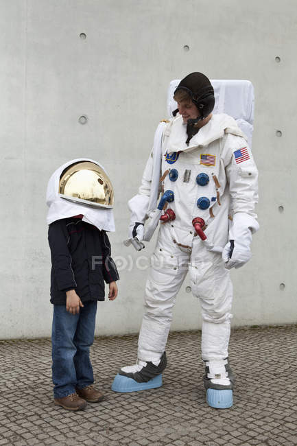 A boy in a space helmet looking up and standing next to an astronaut — Stock Photo