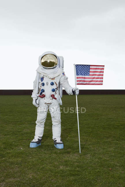 Astronaut standing on lawn and posing with American flag — Stock Photo
