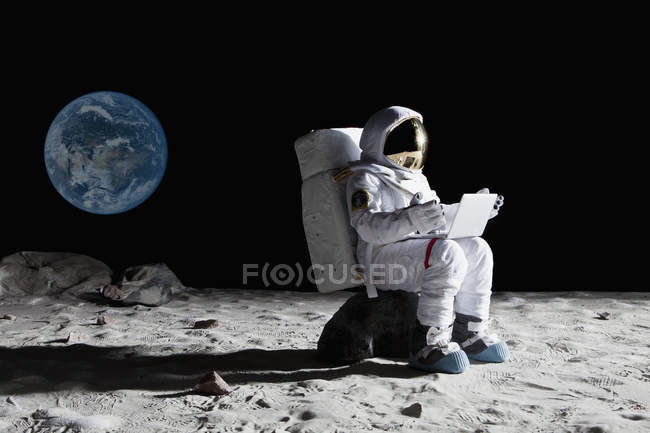 Side view of astronaut sitting on rock and using laptop — Stock Photo
